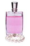 Perfume bottle with a pearl bracelet on white background Stock Images