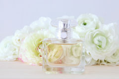 Perfume bottle and pearls necklace next to aromatic flowers. Stock Photo