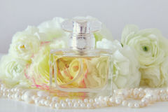 Perfume bottle and pearls necklace next to aromatic flowers Royalty Free Stock Image