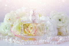 Perfume bottle and pearls necklace next to aromatic flowers Stock Images