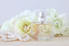 Perfume bottle and pearls necklace next to aromatic flowers Stock Photography