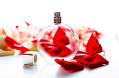 Perfume bottle with petals on table Royalty Free Stock Photo