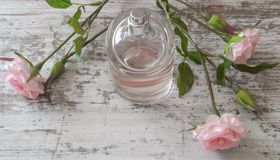 Perfume bottle with a pink fragrance and roses on old wooden background Royalty Free Stock Image