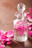 Perfume bottle and pink rose flowers. spa aromatherapy Royalty Free Stock Photography