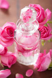 Perfume bottle and pink rose flowers. spa aromatherapy Stock Photos