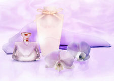 Perfume bottle, ribbon and lilac silk scarf with Orchid flowers Royalty Free Stock Photography