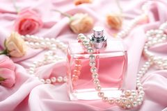 Perfume bottle with roses. And beads on satin background Royalty Free Stock Photos