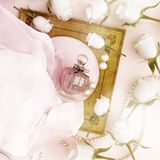 Perfume bottle, roses and pearls located on the folds of pink si. Lk Stock Image