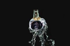 Perfume bottle on water. Splash Stock Photo