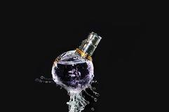 Perfume bottle on water. Splash Royalty Free Stock Photos