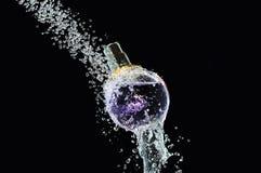 Perfume bottle on water. Splash Stock Images
