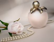Perfume bottle, white rose flower and string of pearls. Royalty Free Stock Photo