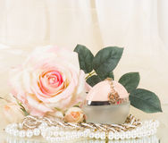 Perfume bottle, white rose and pearls beads Royalty Free Stock Image