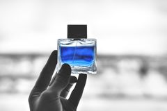 Perfume bottle. In your hand, blue color, background royalty free stock image