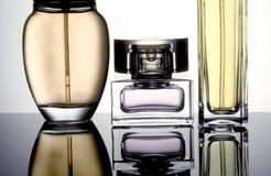 Perfume bottles. On reflective surface Royalty Free Stock Photos