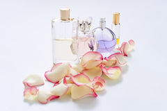 Perfume bottles with flower petals on light background. Perfumery, fragrance collection. Women accessories. Stock Images