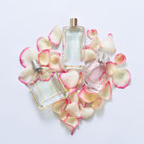 Perfume bottles with flower petals on light background. Perfumery, fragrance collection. Women accessories. Perfume bottles with flower petals on light Royalty Free Stock Photography