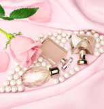 Perfume bottles and flower rose, petals and pearls on pink silk. Stock Photography