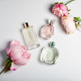 Perfume bottles with flowers on light background. Perfumery, cosmetics, fragrance collection. Flat lay royalty free stock photo