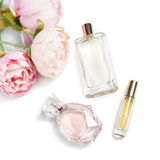 Perfume bottles with flowers on light background. Perfumery, cosmetics, fragrance collection. Flat lay Stock Photos
