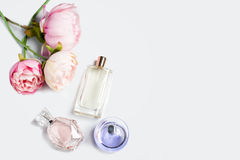 Perfume bottles with flowers on light background. Perfumery, cosmetics, fragrance collection. Free space for text. Royalty Free Stock Images