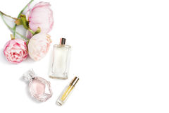 Perfume bottles with flowers on light background. Perfumery, cosmetics, fragrance collection. Free space for text. Perfume bottles with flowers on light Royalty Free Stock Image