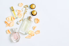 Perfume bottles with flowers petals on white background. Perfumery, cosmetics, jewelry and fragrance collection. Stylized feminine flatlay. Women accessories Royalty Free Stock Images