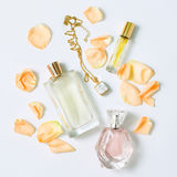 Perfume bottles with flowers petals on white background. Perfumery, cosmetics, jewelry and fragrance collection. Stylized feminine flatlay. Women accessories Royalty Free Stock Photo