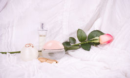Perfume bottles, pink rose and pearls beads Royalty Free Stock Photography