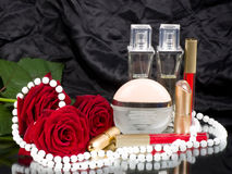 Perfume bottles, pink roses and beads Stock Image