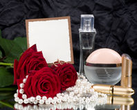 Perfume bottles, pink roses and beads Stock Photography