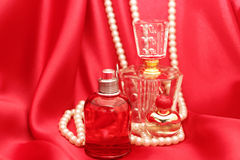Perfume bottles and red satin Stock Photography