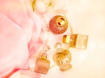 Perfume bottles, roses and pearls located on the folds of  pink Royalty Free Stock Photography