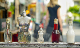Perfume bottles shaped like the female body with a out of focus woman. Walking in the background Stock Photos
