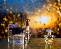 Perfume bottles under the autumn rain with water drops. Perfume bottles under the rain with water drops on the golden table Royalty Free Stock Images