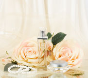 Perfume bottles, white rose and pearls beads Royalty Free Stock Images