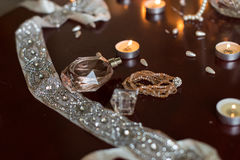 Perfume and a bracelet, burning candles, ribbon with silver stones lying on a wooden table Royalty Free Stock Photography