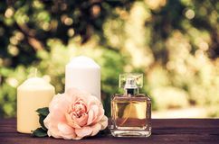 Perfume, candles and flowers on a blurred green background. Spa concept. Romantic concept. Stock Image