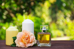 Perfume, candles and flowers on a blurred green background. Spa concept. Romantic concept. Royalty Free Stock Image
