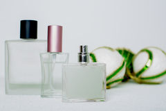 Perfume and Christmas balls over white Stock Photos