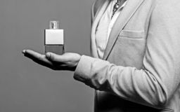 Perfume or cologne bottle and perfumery, cosmetics, scent cologne bottle. Masculine perfume, bearded man in a suit. Man. Perfume, fragrance. Male holding up stock photography