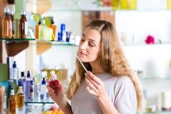 Perfume de compra da mulher na loja ou na loja Fotografia de Stock Royalty Free