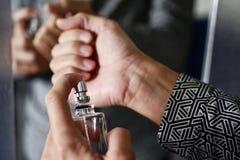 Perfume de pulverização do homem novo em seus pulsos fotografia de stock royalty free
