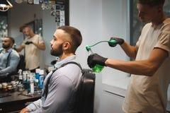 Perfume de rociadura del peluquero en un cliente en un fondo de la barbería Vintage que diseña las herramientas Concepto lujoso d Foto de archivo