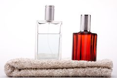 Perfume with decorations. Red and white Aftershave bottles on a towel Royalty Free Stock Images