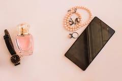 Perfume del ` s de las mujeres en un fondo ligero con los relojes y los accesorios del teléfono Foto de archivo libre de regalías