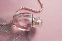 Perfume del ` s de las mujeres en un frasco de cristal con las perlas Fotografía de archivo libre de regalías