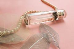 Perfume del ` s de las mujeres en un frasco de cristal con las perlas Imagenes de archivo