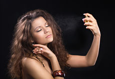 Perfume delight. Beautiful woman enjoying a perfume on black background Stock Photo