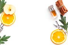 Perfume dulce con fragancia de la fruta Botella de perfume cerca de la manzana, naranja, lavanda, canela en el fondo blanco a imágenes de archivo libres de regalías